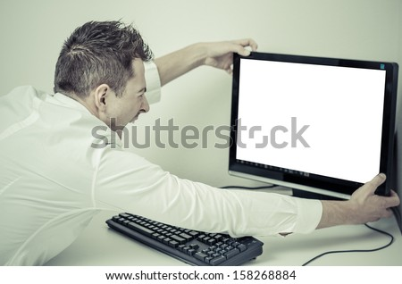 angry man grabbing his computer with a white screen - stock photo