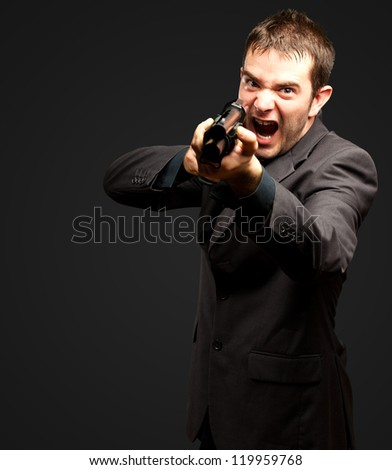 Angry Man Holding Gun against a black background - stock photo