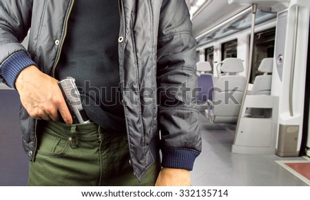 Angry man holding gun in the subway - stock photo