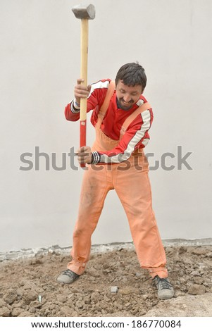 Angry man holding sledge-hammer  - stock photo