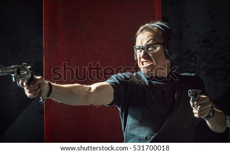 Angry man in a headphones with a gun in his hand on the dark background