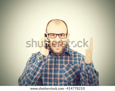 Angry man in glasses yells into  phone. Isolated on gray background. - stock photo
