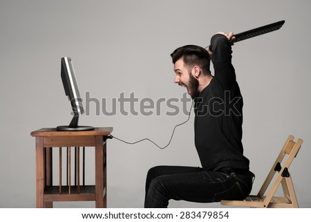 Angry man is destroying a keyboard and monitor of computer on gray background - stock photo