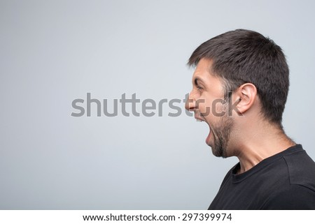 Angry man is evincing his aggression. He is standing in profile and shouting. Isolated on grey background and copy space in left side - stock photo