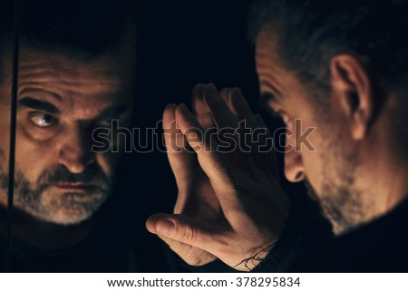 Angry man looking at his reflection in a mirror, in a dark and low light room