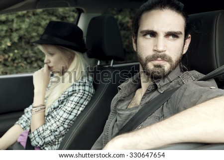 angry man mad at woman after fighting, sitting in car - stock photo