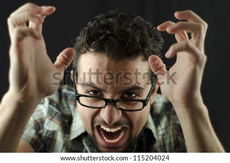 Angry man over dark background - stock photo