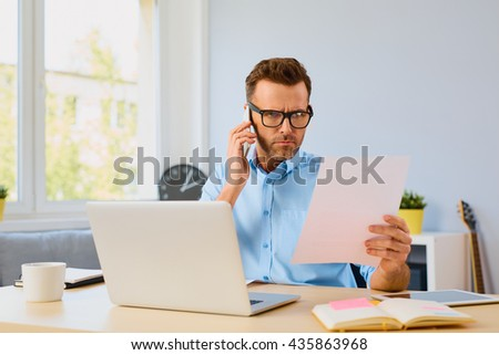 Angry man paying bills and talking on the phone with callcenter - stock photo
