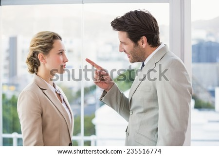 Angry man pointing at his colleague in office - stock photo