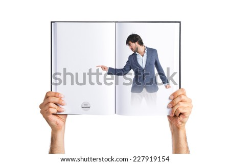 Angry man pointing somebody printed on book - stock photo