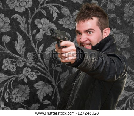 angry man pointing with gun against a vintage background - stock photo