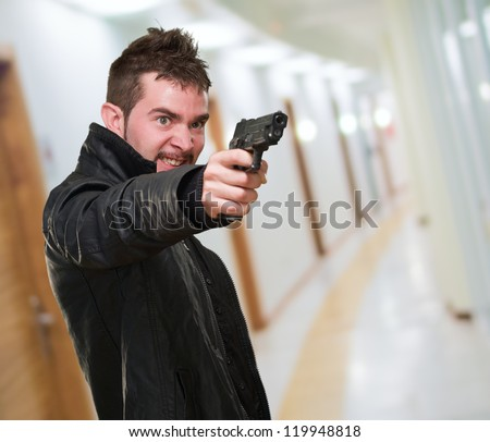 angry man pointing with gun in a passage way