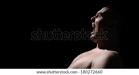 Angry man screaming in extreme rage the dark night - stock photo
