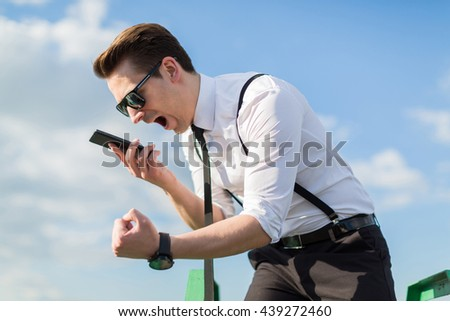 Angry man screams into the phone - stock photo