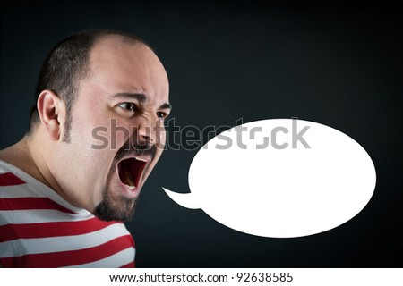 Angry man shouting against black background with white balloon. - stock photo