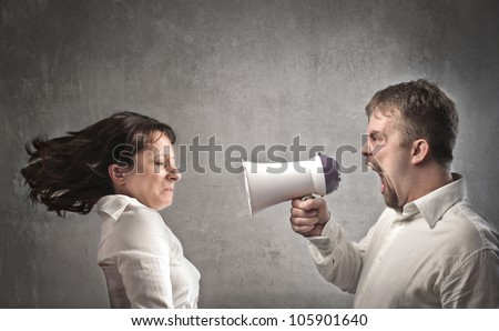 Angry man shouting against his girlfriend with the help of a megaphone - stock photo