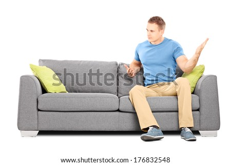 Angry man sitting on couch and swinging his hand violently isolated on white background - stock photo