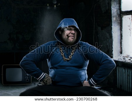 Angry man, sitting with a cigarette - stock photo