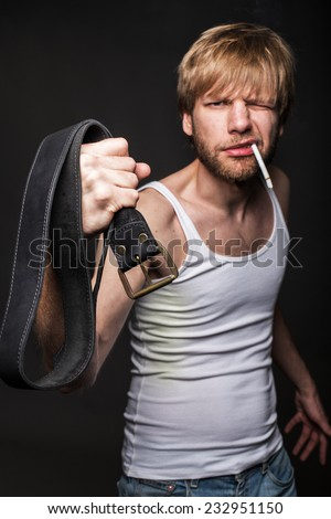 Angry man threatens with belt. Concept: Violence against women. Studio portrait over black background  - stock photo