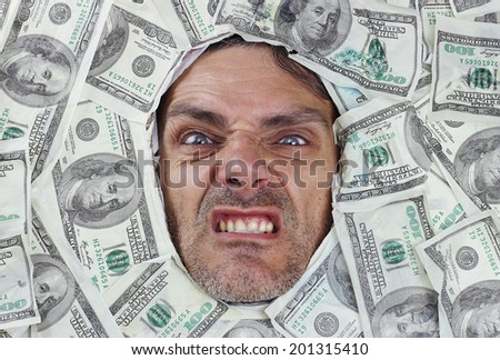 angry man under a bed of dollar notes - stock photo