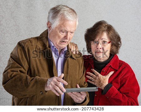 Angry man using tablet with embarrassed woman - stock photo