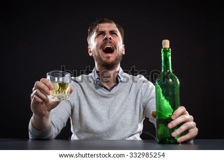 Angry Man With Bottle Holding His Head On Black Background - stock photo