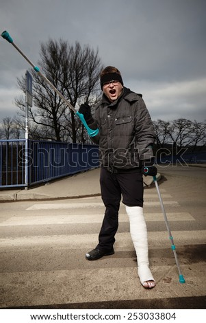 Angry man with broken leg in gypsum hardly move on winter outdoor location with crutches - stock photo
