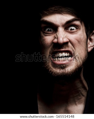 Angry man with grin in the dark - stock photo