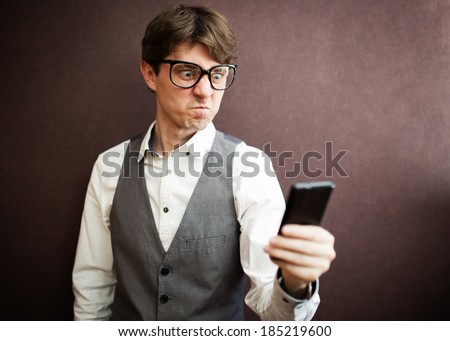 Angry man with mobile smartphone - stock photo