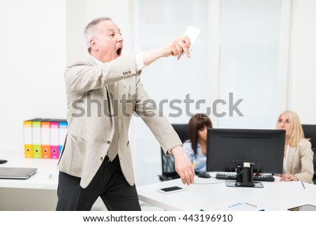 Angry manager throwing away his phone in his office
