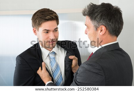 Angry Mature Businessman Holding Coat Of Young Businessman - stock photo