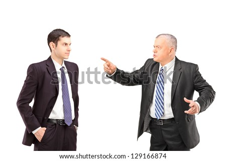Angry mature man in a suit pointing with a finger towards a young man in a suit isolated on white background - stock photo