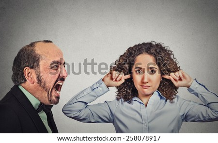 Angry mature man screaming at his young wife who plugs her ears ignoring him isolated on grey wall background. Negative face expression, emotion, confrontation