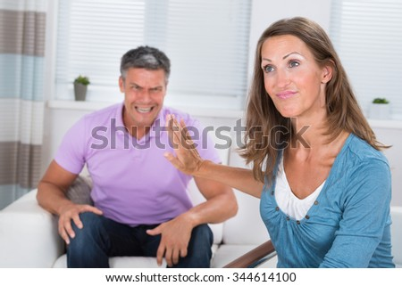 Angry Mature Man Shouting To His Wife In Living Room - stock photo
