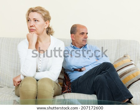 Angry mature married couple having quarrel at living room - stock photo