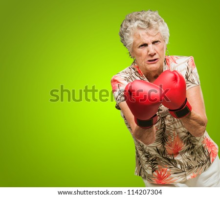 Angry Mature Woman Wearing Boxing Glove Isolated On Green Background