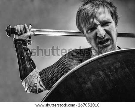 Angry medieval knight armor with a sword and shield, black and white image