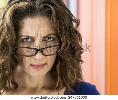 Angry middle aged female teacher frowning over her glasses. - stock photo