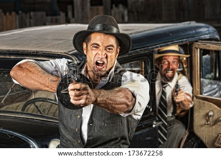Angry mobsters firing submachine gun near antique car - stock photo