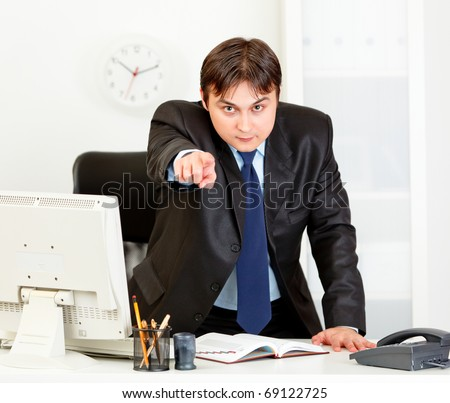 Angry  modern business man standing at office desk and pointing finger on you