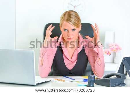 Angry modern business woman sitting at office desk and holding hands near head - stock photo
