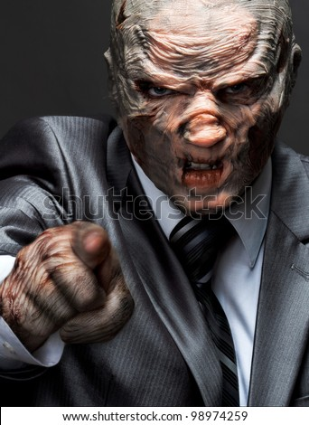 Angry monster in business suit pointing to you