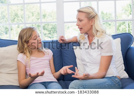 Angry mother scolding daughter while sitting on sofa at home - stock photo