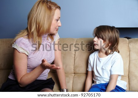 Angry mother talks to her son, give him a serious warning - stock photo