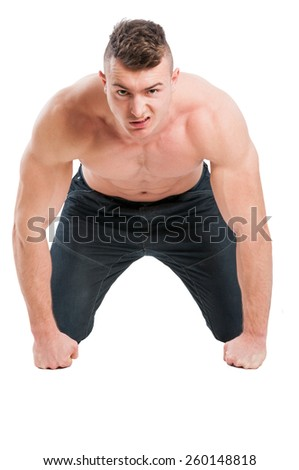Angry muscular male model on all four isolated on white background - stock photo