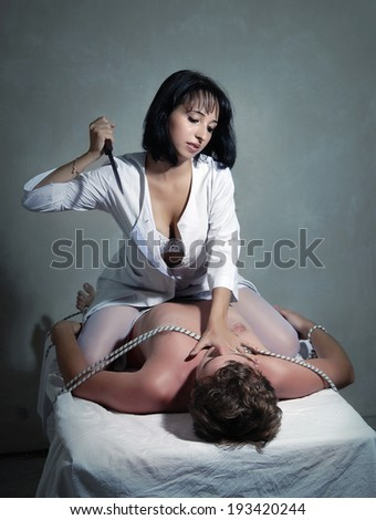 Angry nurse with a knife and bonded man - stock photo