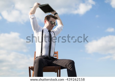 Angry office worker breaks a notebook - stock photo