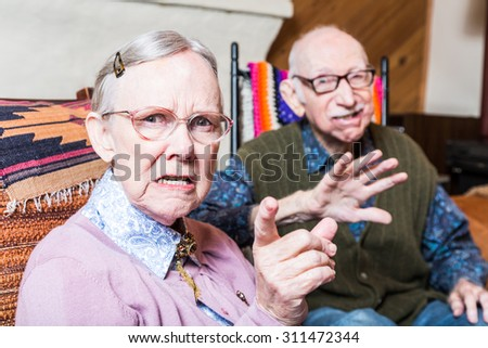 Angry old man and woman scowling at camera sitting in livingroom - stock photo