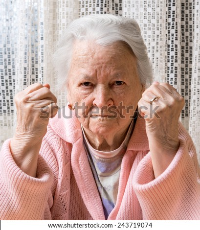 Angry old woman making fists at home - stock photo