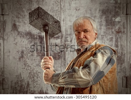 Angry old worker man holding a hammer  - stock photo